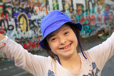 Foto de Cute smiling down syndrome girl on the background of the graffiti wall - Imagen libre de derechos