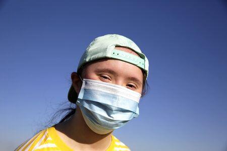 Foto de Girl in a mask on her face on background on a blue sky - Imagen libre de derechos
