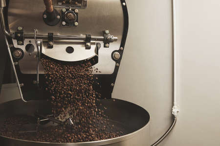 Foto de Hot freshly baked coffee beans fall from best professional large coffee roaster being poured into the cooling cylinder with motion blur on the beans Side centered - Imagen libre de derechos