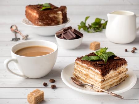 Foto de Tiramisu Dessert with Mint and Cup of Coffee on White Wooden Table. - Imagen libre de derechos