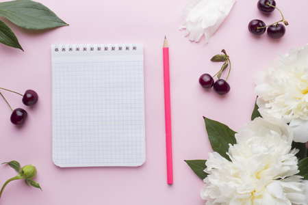 Notepad for text white flowers peony cherry berries on pastel pink background.