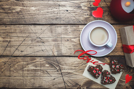 Foto de Concept Valentine's Day. Cup of coffee and cookies on a wooden table. Greeting card Copy space - Imagen libre de derechos