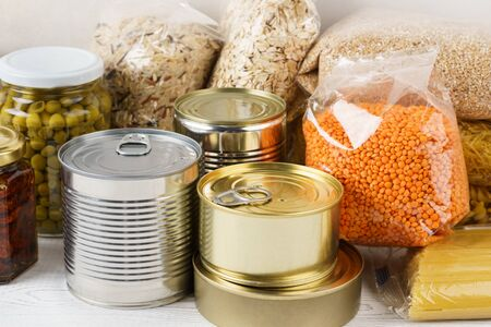 Foto de Various canned food and raw cereal grains on a table. Set of grocery goods for cooking, delivery or donation. - Imagen libre de derechos