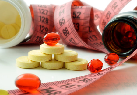 Foto de Measuring tape and bottle with pills. supplements of diet - Imagen libre de derechos