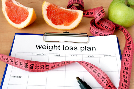 Foto de Paper with weight loss plan and grapefruit - Imagen libre de derechos