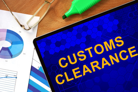 Foto de Tablet with Customs Clearance and charts on a wooden board. - Imagen libre de derechos