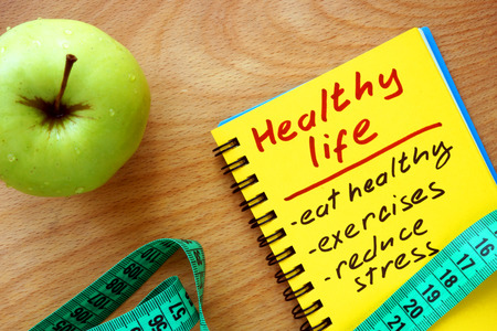 Foto de Notepad with healthy life guide apple and measure tape - Imagen libre de derechos