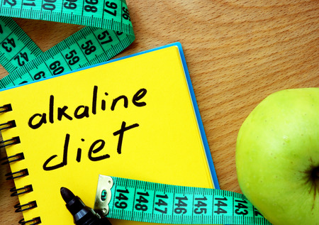 Photo for Notepad with alkaline diet apple and measure tape - Royalty Free Image