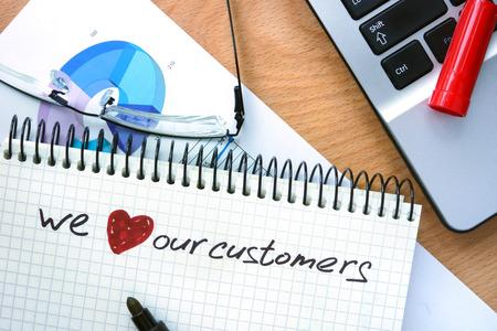 Foto de Notepad with words we love our customers on a wooden background - Imagen libre de derechos