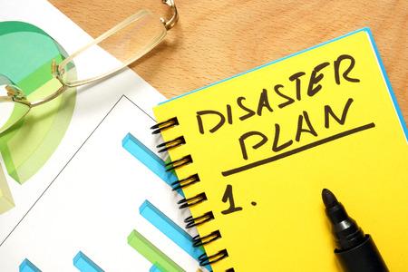 Foto de Notepad with disaster plan on a wooden table. - Imagen libre de derechos