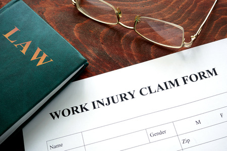 Photo pour Work injury claim form on a wooden table. - image libre de droit