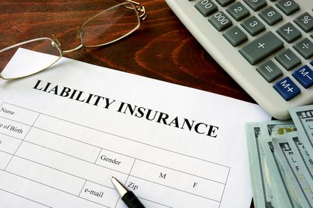 Photo pour Liability insurance  form and dollars on the table. - image libre de droit