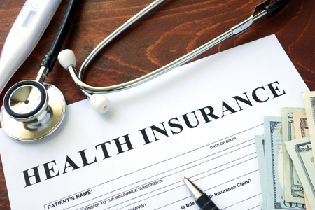 Photo pour Health insurance  form and dollars on the table. - image libre de droit