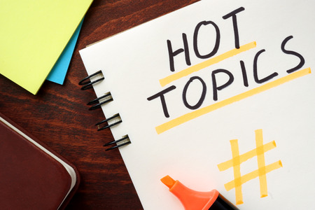 Photo for Hot Topics written in a notepad on a wooden background. - Royalty Free Image