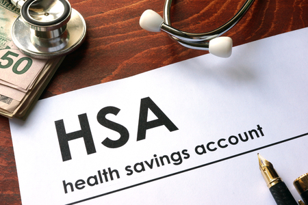 Photo pour Paper with words weekly health savings account (HSA) on a table. - image libre de droit