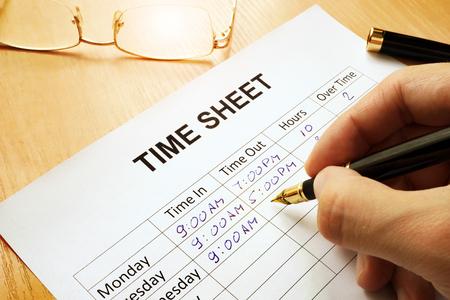 Photo pour Records work hours in a time sheet. - image libre de droit