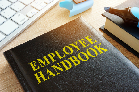 Photo for Employee handbook on a wooden desk. - Royalty Free Image