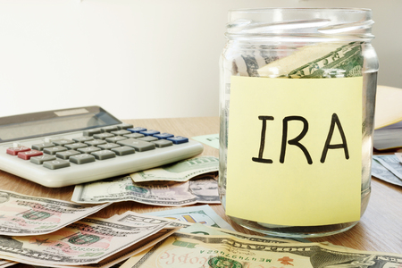 Photo pour IRA written on a stick and jar with dollars. - image libre de droit