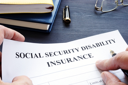 Photo for Man is holding Social Security Disability Insurance SSDI policy. - Royalty Free Image