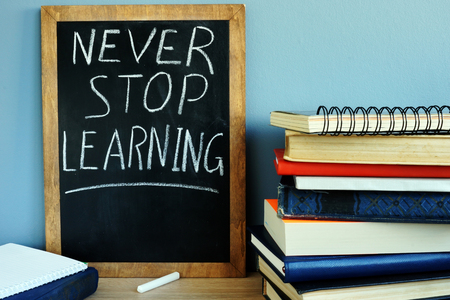 Photo pour Blackboard with sign Never stop learning and books. - image libre de droit