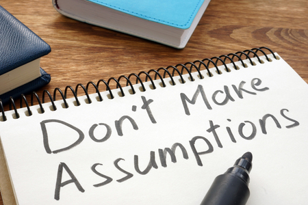 Foto de Don't Make Assumptions. Notepad with marker on a table. - Imagen libre de derechos