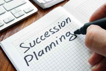 Foto de Man is writing succession planning in the book. - Imagen libre de derechos