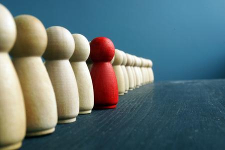 Foto de Leadership development. Line of wooden figurines with red one. - Imagen libre de derechos