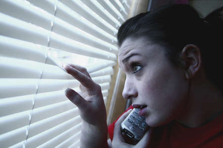 Teenage girl on the phone, looking out the window