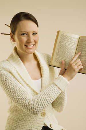 A woman smiling and showing Bible