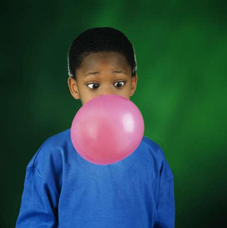 Boy blowing huge bubble with bubble gum