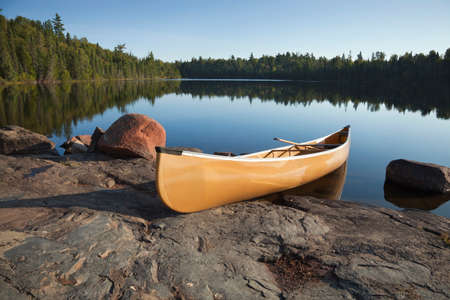 Photo pour A yellow canoe rests on a rocky shore of a calm blue lake in the Boundary Waters of Minnesota - image libre de droit