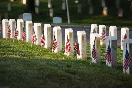 Photo pour Selective focus view of marble grave markers with flags at Arlington National Cemetery on Memorial Day - image libre de droit