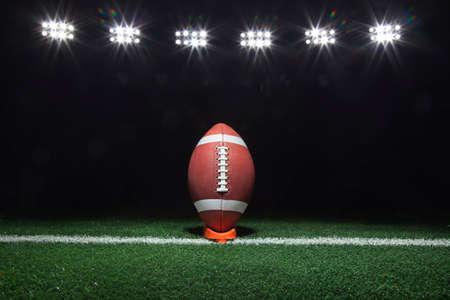 Foto de A football on a tee on a yard line under lights at night - Imagen libre de derechos