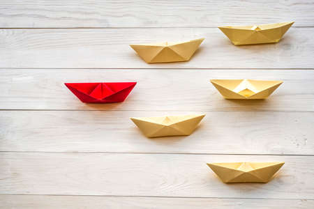 Photo pour leadership concept. origami paper ships following a red boat leader on white wooden background - image libre de droit