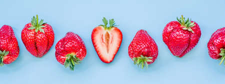 Foto de raw of fresh juicy strawberries on blue background. flat lay top view - Imagen libre de derechos
