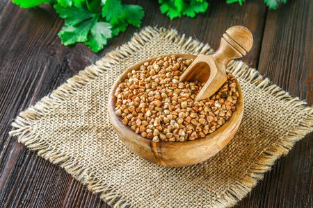 Photo pour Raw buckwheat in wooden bowls and a scoop on sackcloth on a wooden background. Healthy diet food - image libre de droit