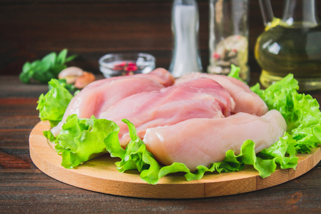 Foto de Raw chicken fillet and green salad on a round cutting board on a wooden table background. Meat ingredients for cooking - Imagen libre de derechos