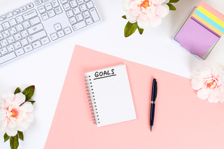 Photo for Write a goal for the new year 2010 in a white notebook on a white desktop next to a coffee mug and a keyboard. Top view, flat layout - Royalty Free Image