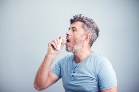 Foto de Spray for sore throat. Photo of a man who treats his throat with a spray and sprinkles it in his mouth. The concept of health and disease. - Imagen libre de derechos