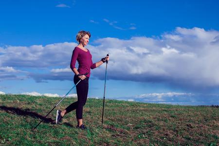 Photo pour Nordic walking, exercise, sport, adventure, hiking concept -a woman hiking in the nature - image libre de droit