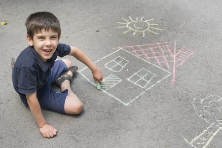 Photo for Child drawing sun and house on asphalt in a park - Royalty Free Image