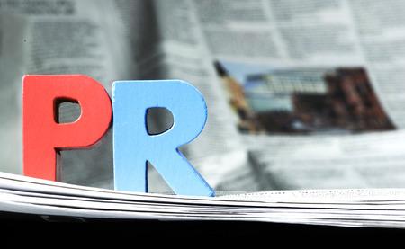 Foto de Word PR on newspaper. Wooden letters - Imagen libre de derechos