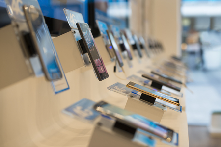 Foto de Smartphones in a shop. Buy smartphone. Telecommunication shop. Showcase with phones - Imagen libre de derechos