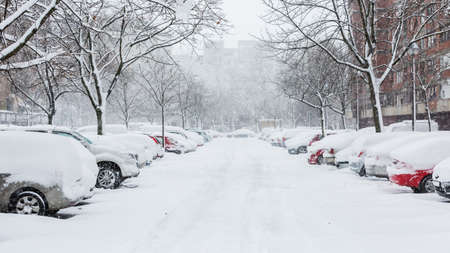 Foto de Cars covered in snow on a parking lot in the residential area during December snowfall - Imagen libre de derechos