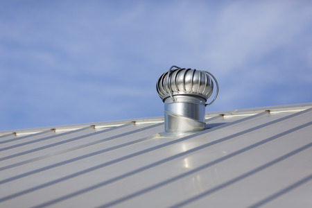 Photo pour Stock photo of an attic vent on a freshly installed, brand new metal roof at a residential home. - image libre de droit