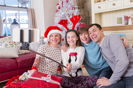 Two Generation Family taking a Selfie at Christmas. They are wearing novelty items and Smiling at the Camera.