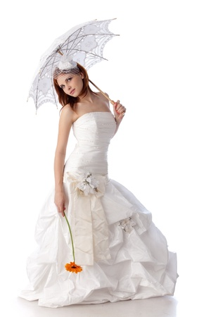 The beautiful young woman in a wedding dress  with umbrella on a white background.
