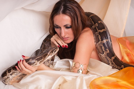 Young beautiful woman with snake lies on the bed.