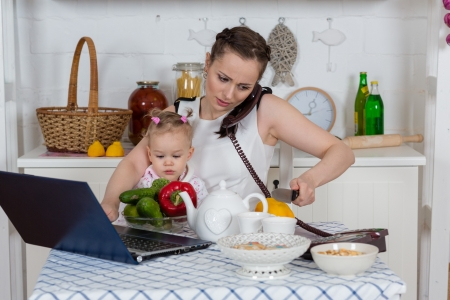 Foto de Young mother  with   little child sit at the dining table in the home kitchen. - Imagen libre de derechos