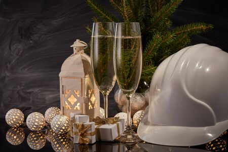 Photo for Construction hard hat, wineglasses with champagne, gift boxes and Christmas ornament on black background. Construction New Year, Christmas background with copy space. For greeting card or advertising - Royalty Free Image